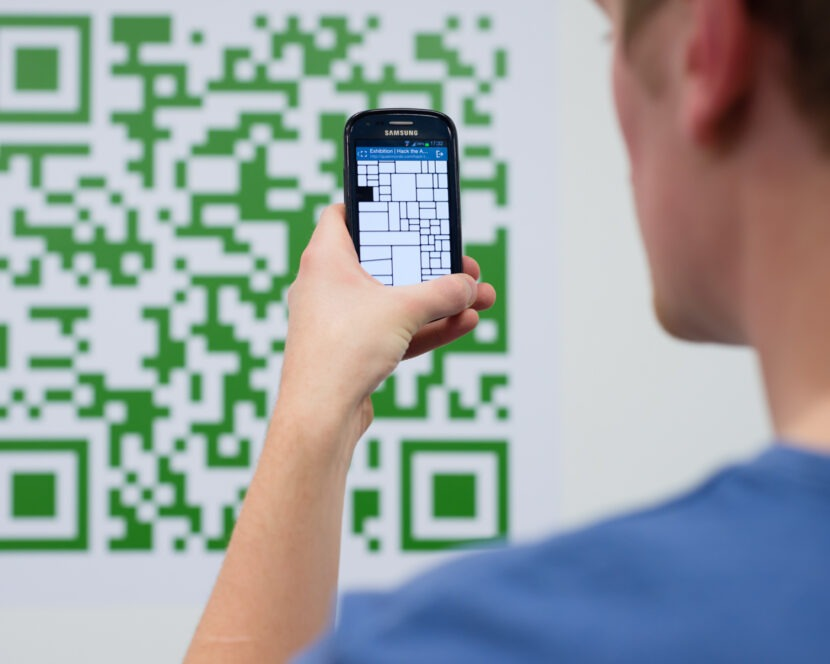 A person in the foreground holds up a phone to capture a QR code in the background.