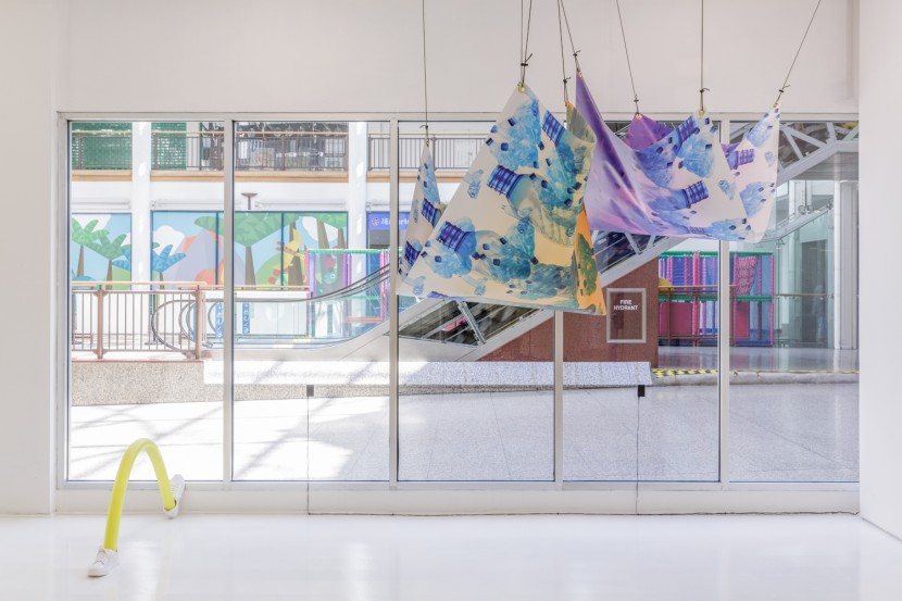 tarp printed with water bottles hanging from gallery ceiling