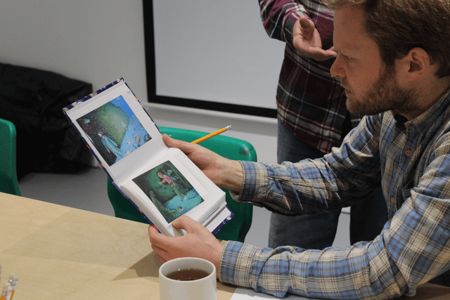 A person holds up an artwork to look at it, with another person in the background