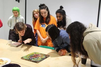 A group of artists huddled together, studying a painting / artwork laid flat on a table.