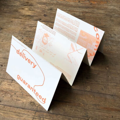 A pale yellow document with red text is folded in a concertina style, it stands on wooden decking.