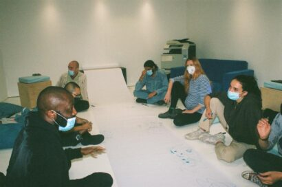 An analogue photograph 8 people sit around a long, blank sheet of paper deep in discussion
