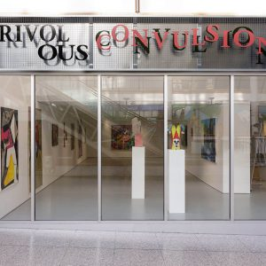 Turf's shop frontage window, showing an exhibition within. The exhibition signage above the window says 'Frivolous Convulsions' in jumbled text.