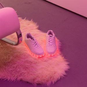 a pair of white light-up shoes on a faux fur rug