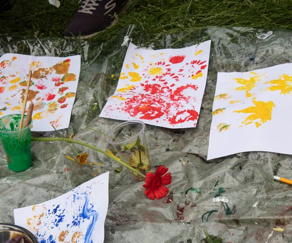 4 pieces of paper with prints of flowers are laid out on a plastic sheet on some grass