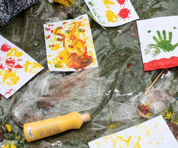 5 pieces of paper with painted flower prints laid to dry on a plastic mat