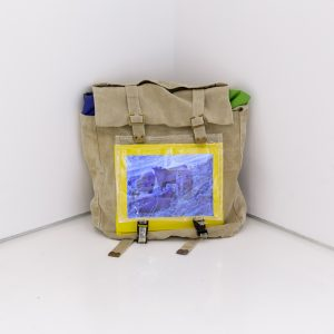 'Bug Out Bag' Mette Boel Screen with 41 digital images (on loop), custom-made army bag, rain proof fabric, plastic, clasps 30 x 35 x 20 cm 2018