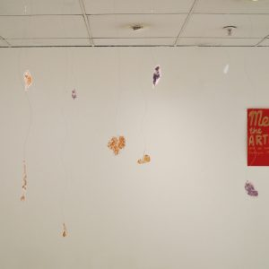 Blue and gold printed leaves suspended from the ceiling. In the background there is a red piece of paper hanging on the wall saying 'Meet the Artists'.