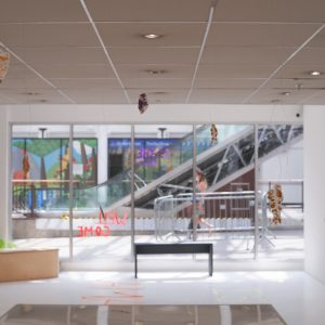 Installation view of the gallery facing out. The escalators are visible through the window. There is a glass vitrine in the foreground and a bench in the background.