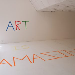 Colourful tape on the wall and floor that spells out 'Art is Amazing'.