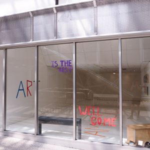A shot of the outside of the Turf Projects gallery. On the window is written, 'Art is the best' and 'Well come'.