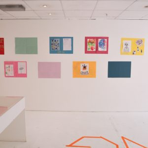 Nine colourful pieces of art on the wall in two overlapping lines.