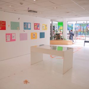 A shot of the gallery from a 45 degree angle. The glass vitrine is visible and the nine colourful pieces of art work on the wall.