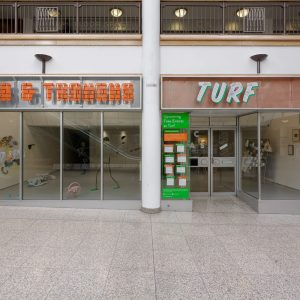 Photograph of the outside of Turf Projects' space, with the signage reading 'Turf' in green and white with black overlaid lines, based on the logo on the outside. To the left of 'Turf' above the exhibition's shop front window is the signage for the exhibition 'Peaks & Troughs' in orange bubble style lettering with a black grid pattern overlaid on each letter.