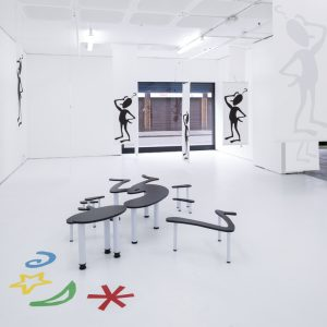 Black human figures displayed standing and on stands on the floor