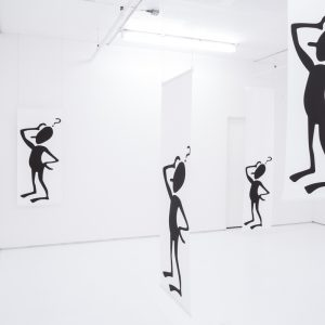 Black human figures hanging on fabric