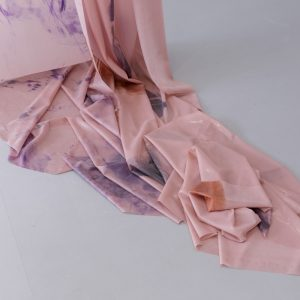 Detail of hanging pink fabric with purple prints