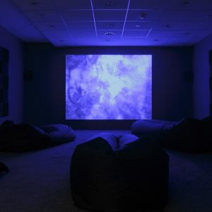 a blue projector screen in a dark room