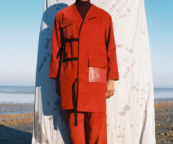 Man stood in red in front of a sheet on a beach